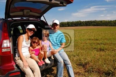 Familia de cuatro personas cerca de su coche de vacaciones