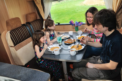 Familia que come en RV interior, viajar en campista de vacaciones
