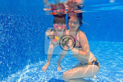 Familia sonriente bajo el agua que se divierten en la piscina