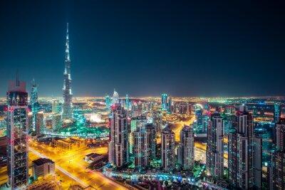 Póster Fantástico horizonte nocturno de Dubai con rascacielos iluminados. Perspectiva de la azotea de Dubai céntrica, UAE.