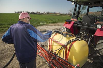 Farmer vertiendo agua en el pulverizador tractor en el campo