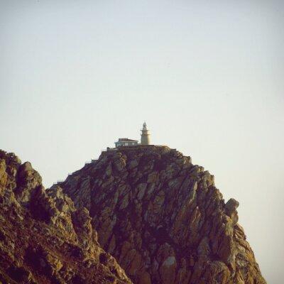 Póster Faro en la parte superior del acantilado de piedra
