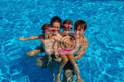 Feliz familia de cuatro que se divierten en la piscina