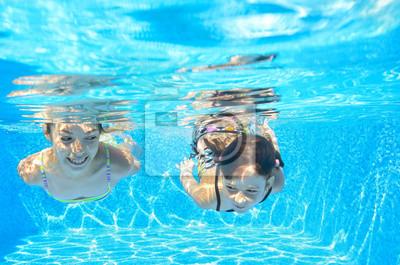 Feliz niñas nadan bajo el agua en la piscina, que se divierten en vacaciones