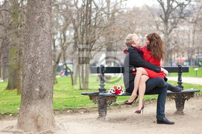 Feliz pareja abrazando romántica en un banco