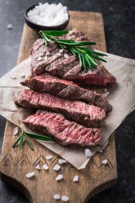 Póster Filete de carne a la parrilla con romero y sal en la tabla de cortar