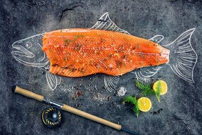 Póster Filete de pescado de salmón crudo con ingredientes como limón, pimienta, sal y eneldo en tablero negro, la imagen esbozada con tiza de pescado de salmón con carne y caña de pescar