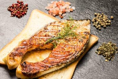 Póster Filete de salmón a la parrilla sobre rebanada de pan caliente y especias sobre la pizarra