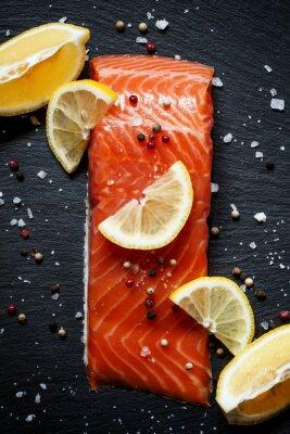 Póster Filetes de salmón deliciosos con limón, sal marina y pimienta en un da
