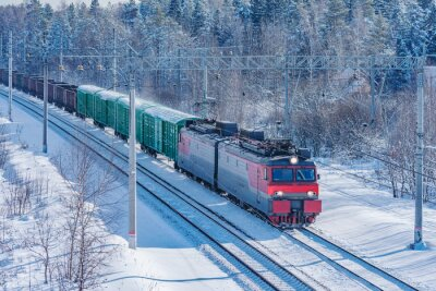 Freight train moves at sunny winter day time.
