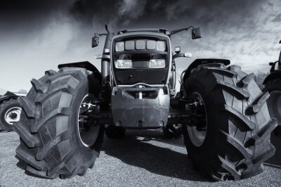 Póster Gran tractor agrícola bajo un cielo tormentoso