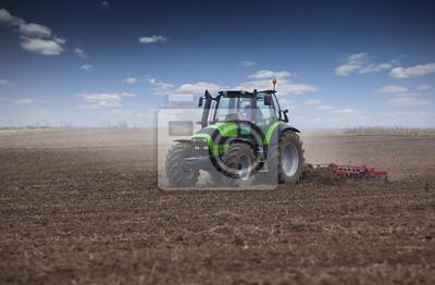 Granjero joven en tractor tierra se prepara para la siembra