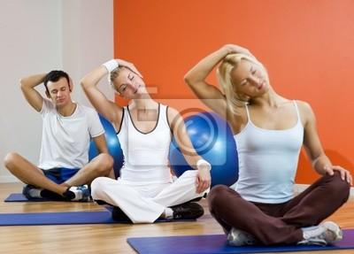 Grupo de personas que hacen ejercicio de yoga (atención a la mujer en el middl