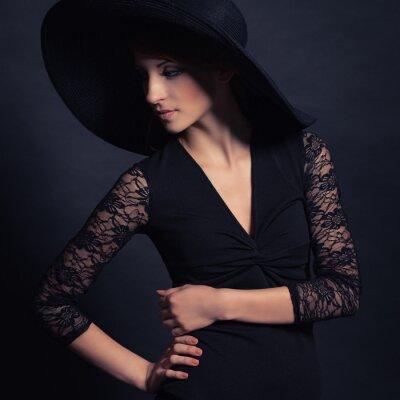 Póster hermosa chica en traje negro y sombrero