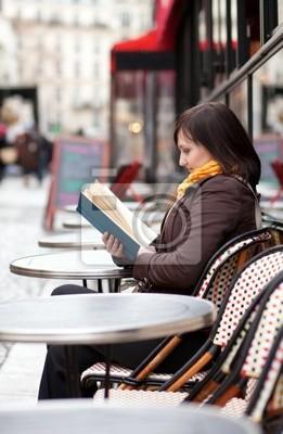 Hermosa chica joven que lee un libro en un café parisiense de la calle