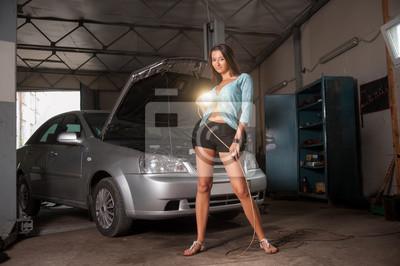 Hermosa chica sexy de pie cerca de coche en el taller de reparación de coches