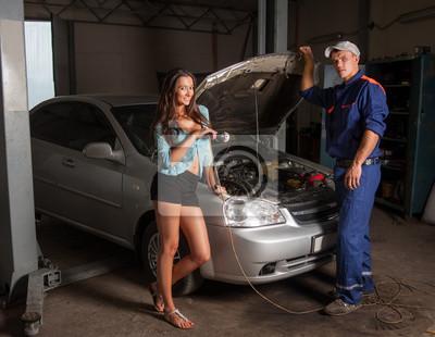 Hermosa chica y mecánico de automóviles de pie cerca del coche con abierto