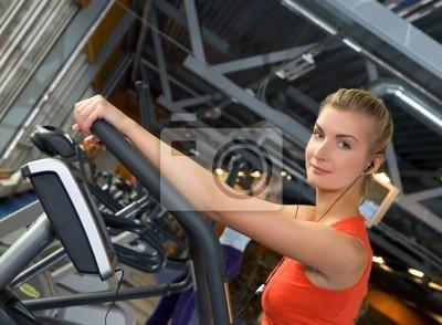 Hermosa joven haciendo ejercicio en un gimnasio mientras escucha