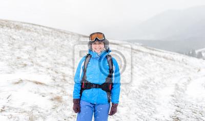 hermosa muchacha sonriente en la cima de las montañas cubiertas de nieve