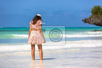 Hermosa mujer con un sombrero en una increíble playa de agua verde en Zanzíbar en Tanzania