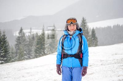 hermosa niña en la parte superior de las montañas cubiertas de nieve mirando cámar