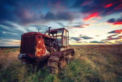 Póster Hermosa puesta de sol sobre el campo y el viejo tractor oxidado
