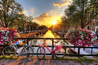 Póster Hermoso amanecer en Ámsterdam, Países Bajos, con flores y bicicletas en el puente en primavera