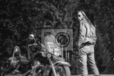 Hermoso hombre brutal con el pelo largo y la barba de pie cerca de la motocicleta. Biker está usando chaqueta de cuero y gafas de sol en día soleado. Vista trasera. Efecto suave de cambio de inclinaci