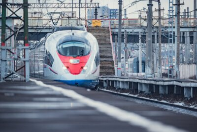 Highspeed train approaches to the station platform at winter day time.