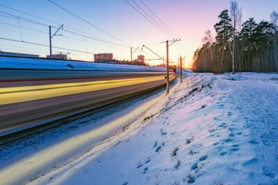 Highspeed train moves fast at winter sunset time.