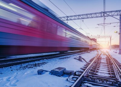 Highspeed train moves fast through the station at winter sunset time.