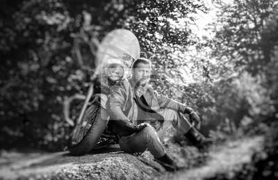 Hombre barbudo posando con su moto crucero por encargo elegante brillante. Biker está sentado en el suelo cerca de su bicicleta con chaqueta de cuero, guantes y botas. Efecto suave de cambio de inclin