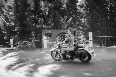 Hombre con barba conduciendo su moto crucero por carretera agradable en el bosque. El hombre lleva chaqueta de cuero y vaqueros. Vista trasera. Efecto de desenfoque de la lente de cambio de inclinació