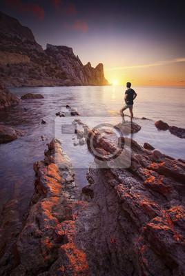 Hombre de pie sobre una piedra en una bahía de mar