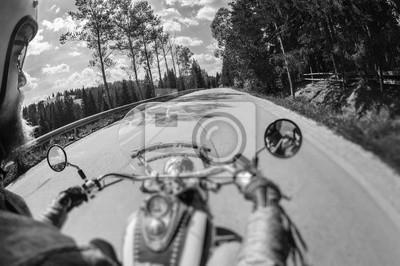 Hombre del motorista que monta su moto en el camino abierto para arriba en las montañas, guantes de cuero que desgastan. Imagen en movimiento. Vista en primera persona. Tablero brillante de plata. Efe