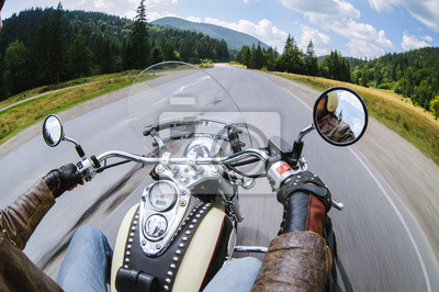 Hombre del motorista que monta su moto en el camino abierto para arriba en las montañas, guantes de cuero que desgastan. Imagen en movimiento. Vista en primera persona. Tablero brillante plateado