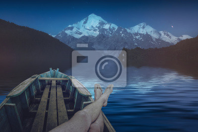 Hombre descansando en un lago alpino