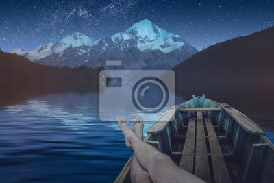 Hombre descansando en un lago alpino en la noche