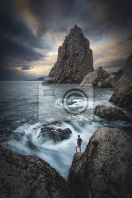 Hombre en un borde de acantilados sobre el mar. Instagram stylization