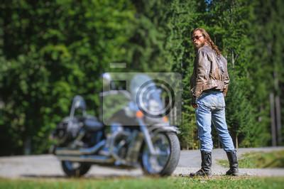 Hombre guapo con el pelo largo y la barba de pie cerca de su motocicleta de crucero por encargo. Biker está usando chaqueta de cuero y gafas de sol en día soleado. Efecto suave de cambio de tilt