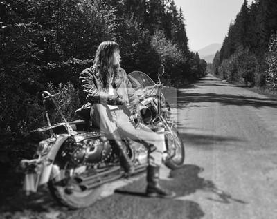 Hombre joven del motorista con el pelo largo y la barba que desgasta una chaqueta de cuero guantes y cargadores del programa inicial que se sientan en su motocicleta en el camino abierto. Día soleado