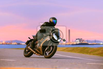 hombre joven que monta el deporte viajar a la motocicleta en las carreteras de asfalto ag