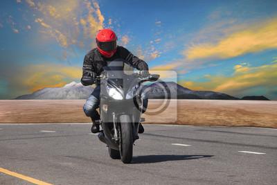 hombre joven que monta la motocicleta en el asfalto utilización curva de la carretera para extrem