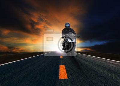 hombre joven que monta la motocicleta en la carretera de asfalto