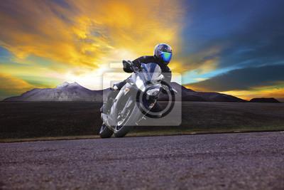 hombre joven que monta la motocicleta en la curva de la carretera de asfalto con las zonas rurales y