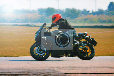 hombre joven que monta la motocicleta en la curva de la carretera de asfalto con un mo
