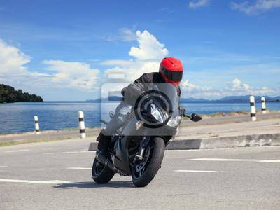 hombre joven que monta motocicleta grande bicicleta contra curva pronunciada de asph
