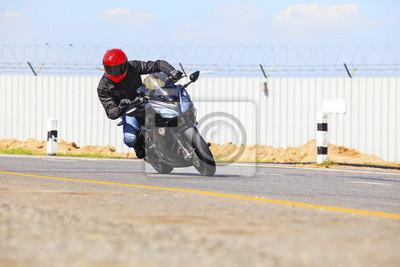 hombre joven que monta motocicleta grande bicicleta en agudo camino de la curva del asfalto