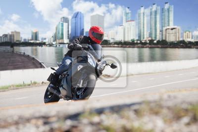 hombre joven que monta motocicleta grande moto en la carretera de la ciudad contra urbano