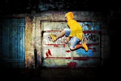 Póster Hombre joven que salta / baile en el fondo del grunge pared de graffiti